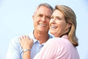 A couple smiling confidently with the help of dental implants.