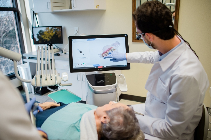 A photograph of prosthodontist Dr. Tostado treating a patient and looking at a monitor screen. Is he the best dentist in San Antonio?