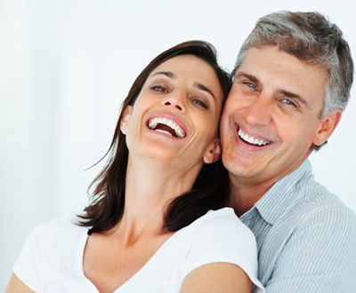 A couple smiling and demonstrating the benefits of having full-mouth reconstruction.