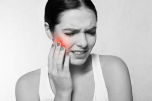 A woman in pain from a toothache, holding her hand to the side of her face. The painful area is highlighted in red for dramatic effect.