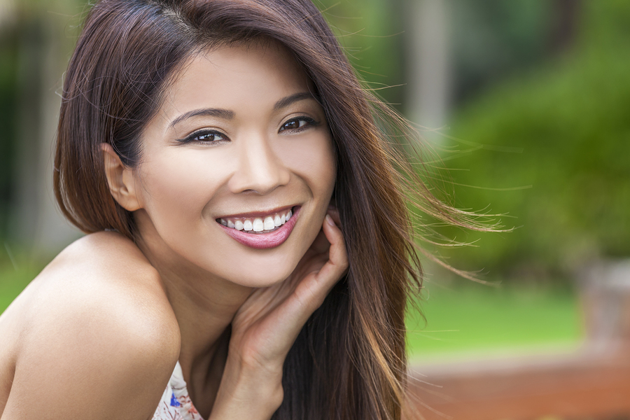 A young woman smiling outside. CEREC crowns can enhance your smile in just one appointment.