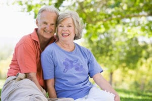 An older couple sitting outdoors and smiling. Adults of any age who've lost their teeth can smile confidently with new dentures.