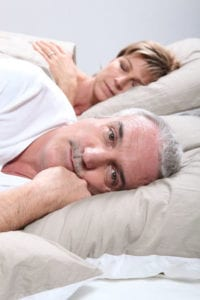 An older man lies awake because of having sleep apnea.